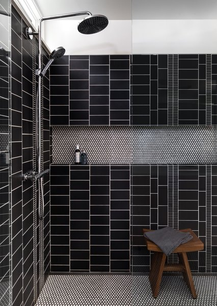 A custom mix of graphite tiles from Ann Sacks line the walls of the master bath. The floors are white penny rounds from American Universal Corporation.
