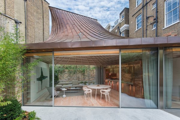The sculptural roof appears to float above the glass-walled living space on the ground floor.