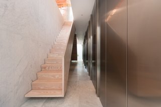 The Dinesen staircase descends along a wall of fluted Carrara marble.
