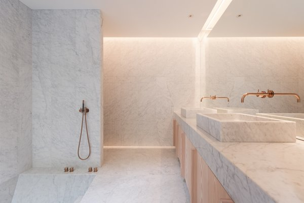 The master bath features a double shower and a sunken marble bathtub that overlook views of a glass-walled winter garden.