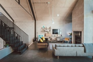 Jon's living room is anchored with a double-faced concrete masonry chimney with indoor and outdoor functionality. The steel stairs on the left lead up to a mezzanine study area.