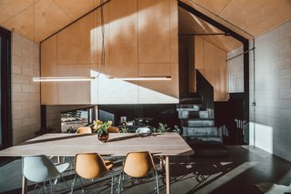 The dining area is located a split-level above the kitchen in Nik's home. The plywood-clad volume above houses the master bedroom.