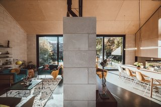A concrete masonry wall divides the dining area from the living room. As in Jon's house, walls of glass open up the living spaces to the millpond.