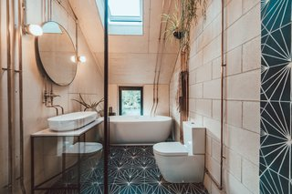 A peek inside the adjoining master bathroom decorated with Marrakesh Design wall tiles, air plants and exposed copper piping.