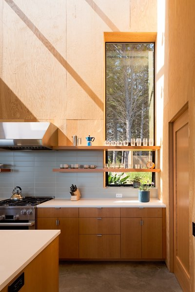 The kitchen is outfitted with a Wolf stove and hood, Hansgrohe faucet, and Sugatsune cabinetry hardware.