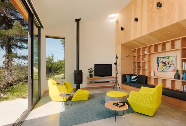 A Jøtul Direct Vent Gas Stove anchors the living space that seamlessly connects with the outdoors through massive, operable glazing by Fleetwood. Aside from the custom built-in bench, the chairs and furnishings are by Ligne Roset.