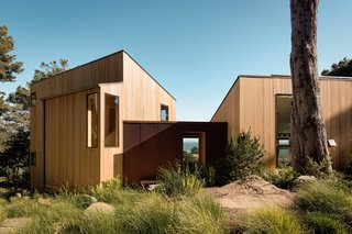 Corrugated Cor-Ten steel clads the entryway that connects the two cedar-clad wings.