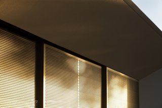 A series of sliding, perforated, bronze screens let in dappled light while providing privacy and protection from the sun.