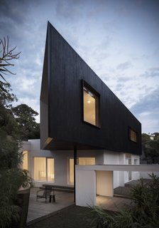 The extension's dark cypress cladding was charred on-site by hand.