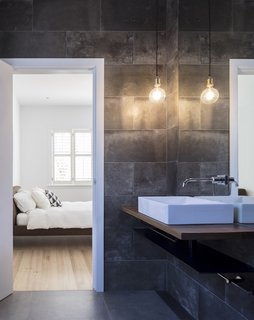 In the master bathroom, dark stone differentiates the space from the rest of the bright interiors. All bathrooms include electric underfloor heating.