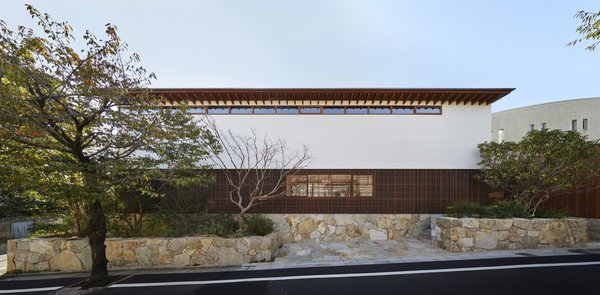 The home is concealed behind horizontal bands of materials including Aji stone quarried from Shikoku, a powder-coated aluminum screen (lath), the white plaster exterior of the second floor, and a titanium zinc alloy roof.