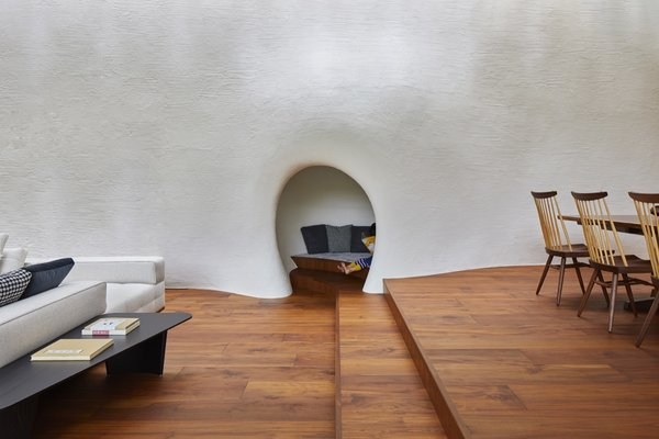 The white plaster inside the home signals a continuation of the outdoor facade. The cave-like nook was inspired by the fireplace in Swedish architect Erik Gunnar Asplund's summer house.