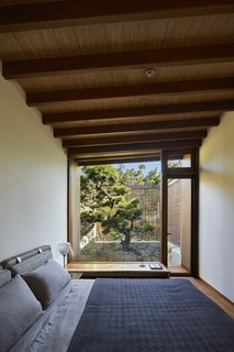 The guest bedroom, located on the south side of the site, overlooks a Japanese pine tree.