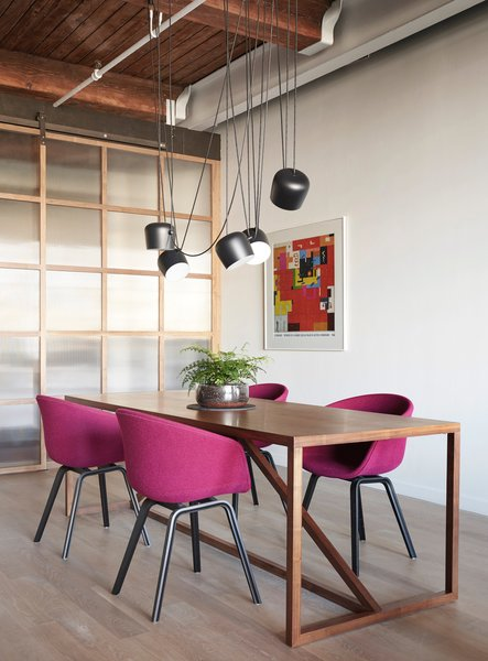Flos lighting hangs over a BluDot dining room table with Hay dining chairs.