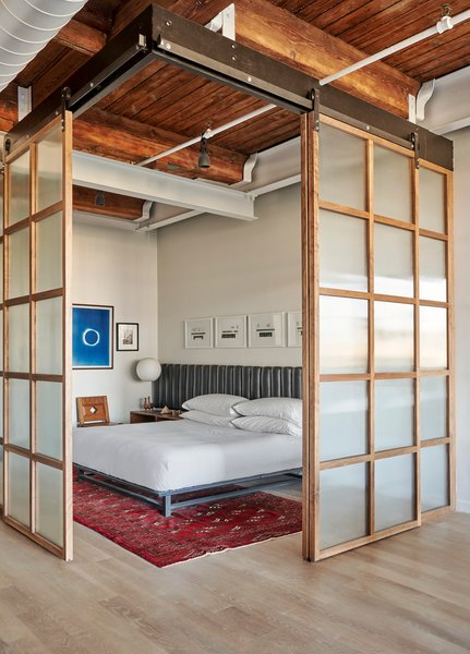 Sliding walnut panels with reeded glass inserts enclose the bedroom area.