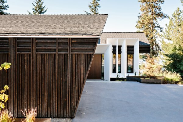 The roof is sheathed in asphalt shingles and is complemented by charred timber siding.