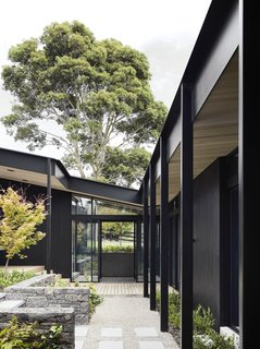 """Three elongated blackened timber pavilions form a U shape, encompassing the external courtyard and identifying strongly with the site narrative and notions of a working yard or arena,"" the architects explain."