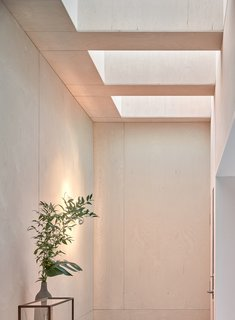 The white-washed Baltic birch plywood coffered ceiling is fitted with Velux skylights that bathe the work room in natural light.