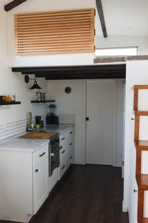 The loft bedroom is located above the galley kitchen and bathroom, and is accessed via stairs with built-in shelving.