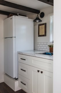 A Vissiani refrigerator stands next to the kitchen's formica countertops. The lights are from Ecopower.