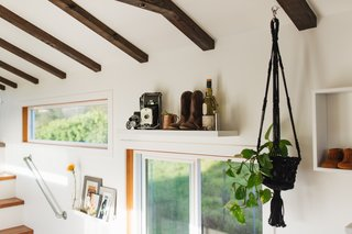 """The exposed ceiling beams pop against the all-white interior. Zeena adds, """"The one design element that I love so much is how we wrapped the interior window sills with stained wood. With so much white in our home, this element adds an interior warmth, especially when the sun hits it."""""""