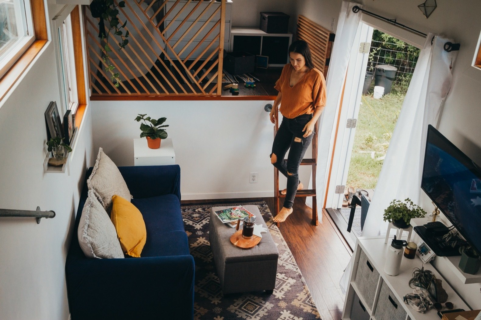 Living, Medium Hardwood, Coffee Tables, Sofa, Rug, Bench, Shelves, End Tables, and Wall Custom-built from the ground up, a 360-square-foot tiny house on wheels is an affordable, off-grid paradise for a family of three in Hawaii.  Living Bench Medium Hardwood Wall Photos from Budget Breakdown: A Maui Couple Build an Off-Grid Tiny Home For $45K