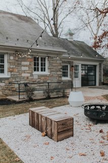 After cleaning up the landscape, the team custom-made a few benches  for the backyard and added gravel from Penn's Stone Supply. The string lights and West Elm Planters add a stylish touch.