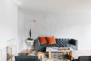 Some of the living room walls were painted with a gray lime wash by Portola Paints, while other walls were finished with Nebulous White by Sherwin Williams. The pink, wall-mounted light is from Anthropologie.