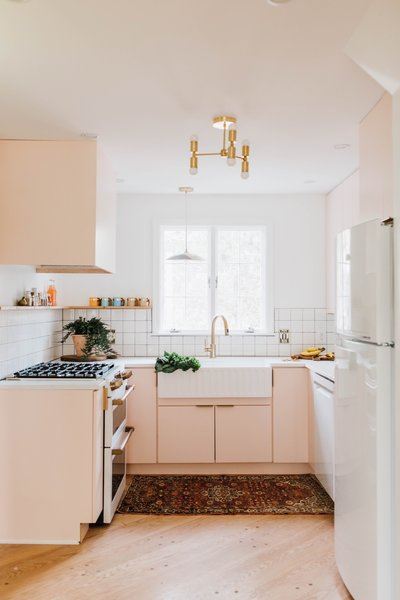At a renovated home in Pennsylvania, the orange kitchen countertops were swapped for custom concrete countertops. The cabinets were painted Pink Ground by Farrow & Ball and paired with Build.com hardware, giving the kitchen a warm glow, in particular thanks to the natural light coming in from the double exposure of the windows. The kitchen sink and faucet are from Amazon, while the tile is from Lowes.