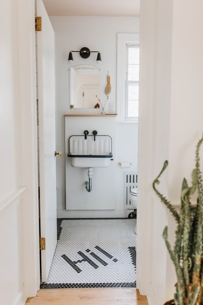 The updated hallway bathroom has a lot more personality with a Rejuvenation sink, a Wayfair faucet, and playful floor tile from a local tile shop. For a pop of color, the ceiling was painted Pink Ground by Farrow & Ball.