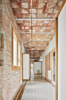 A glimpse down the hallway, where the architects say the original construction is best appreciated. Here, the hallway shows off brick walls, Catalan-style arches, iron beams, and original window frames.