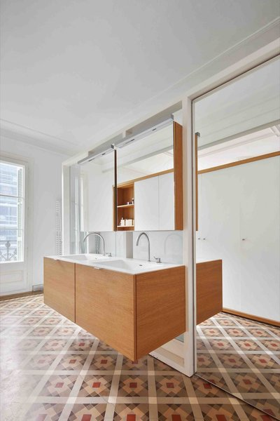 The bathroom furniture and cabinetry are built of oak, while the countertops are made from solid white resin.
