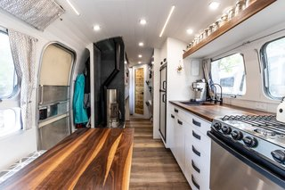 A view from the front of the Airstream towards the angled bathroom door in the rear. Note the small closet, perfect for hanging coats and boots, slotted between the door and the wood stove.