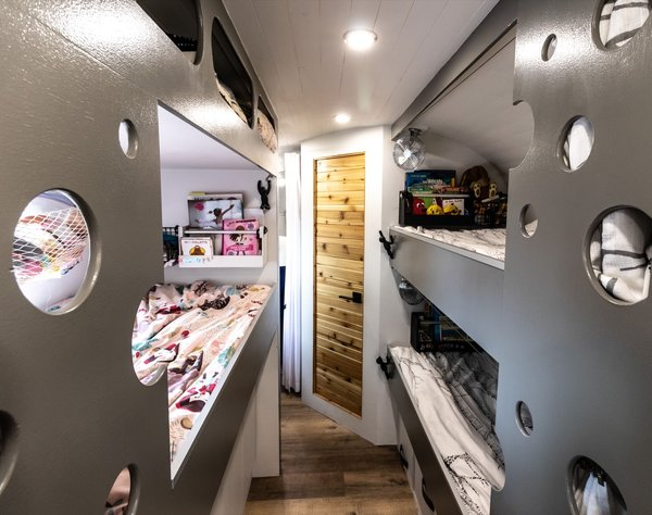 """The """"kids' area"""" in the heart of the Airstream features three bunk beds fitted with twin-size IKEA foam mattresses, built-in storage, and privacy curtains. The round cutouts reference the Airstream's rounded shape and the portholes in ships."""
