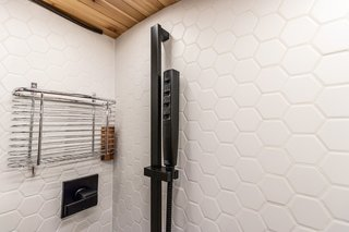 The full shower, surrounded by ceramic tiles, is connected to an on-demand propane water heater.