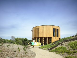 Wild bush, sand dunes, and scrub surrounds the circular home. The architects were careful to minimize the building impact on the fragile landscape.