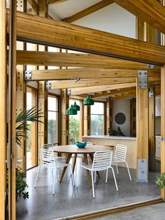 The architects left part of the upper level open to turn the dining area and part of the outdoor patio into airy, double-height spaces.