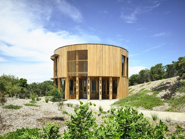 To take in views of Victoria's coastline from all directions, Austin Maynard Architects crafted a bach-inspired beach house using a circular, corridor-free design and full-height glazing. Exposed trusses and a simple material palette keep focus on the outdoors, while rooftop solar panels and a rainwater harvesting system help the dwelling reduce site impact.