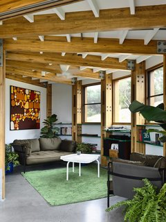 The cozy living room pulls the outdoors in with its earthy palette and abundance of indoor greenery.