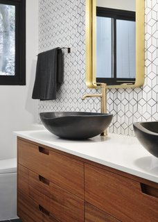 The renovation introduced new plumbing and lighting fixtures selected by NMT Financial, custom wood vanities designed by See Arch, and new tiled walls installed in all bathrooms.