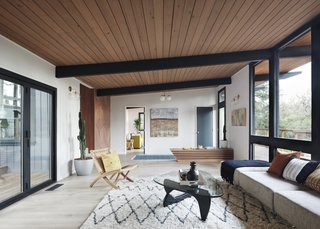 The updated living room features new wide-plank white oak hardwood floors, a refinished wood ceiling and structural beams, and new sheetrock finished walls to replace original wood paneling for a brighter look.