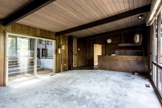 The dated living room was constricted with timber on all sides.