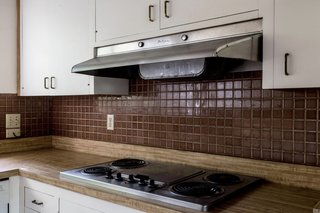 """A look at the dated kitchen. <span style=""""font-family: Theinhardt, -apple-system, BlinkMacSystemFont, """"Segoe UI"""", Roboto, Oxygen-Sans, Ubuntu, Cantarell, """"Helvetica Neue"""", sans-serif;"""">All the pictured elements were swapped out</span><span style=""""font-family: Theinhardt, -apple-system, BlinkMacSystemFont, """"Segoe UI"""", Roboto, Oxygen-Sans, Ubuntu, Cantarell, """"Helvetica Neue"""", sans-serif;"""">for new materials and appliances.</span>"""