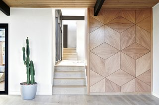 """A geometric wood accent wall <span style=""""font-family: Theinhardt, -apple-system, BlinkMacSystemFont, """"Segoe UI"""", Roboto, Oxygen-Sans, Ubuntu, Cantarell, """"Helvetica Neue"""", sans-serif;"""">built by Greenport Designs</span><span style=""""font-family: Theinhardt, -apple-system, BlinkMacSystemFont, """"Segoe UI"""", Roboto, Oxygen-Sans, Ubuntu, Cantarell, """"Helvetica Neue"""", sans-serif;"""">lies across from the main entry wall and runs alongside the stairs.</span>"""