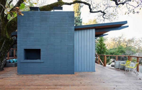 See Arch restored the exterior fireplace wall and painted it a deep blue hue to match the repainted blue timber cladding.