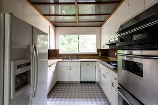 Despite the large window framing the outdoors, the existing U-shaped kitchen felt cramped compared to modern kitchens.