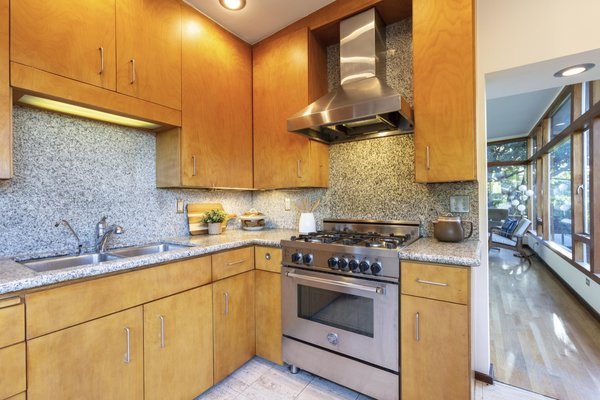 The backsplash and countertops are made from granite. Terrazzo marble lines the kitchen floor.