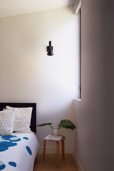 An Alvar Aalto stool serves as a side table in the bedroom. The north-facing window brings in ample natural light.