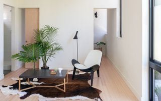 The living room is simply furnished with an IKEA cowhide rug, a France and Son floor lamp, a replica of the Hans Wegner CH07 Lounge Chair, and tropical plants for a pop of color. Double pocket doors provide privacy.