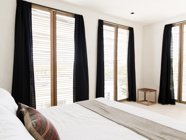 Floor-to-ceiling slatted wooden shutters flood the rooms with natural light.
